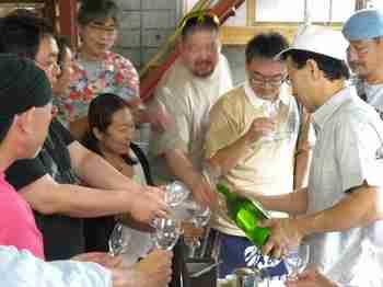 濁り酒の上澄みを注ぐ工場長